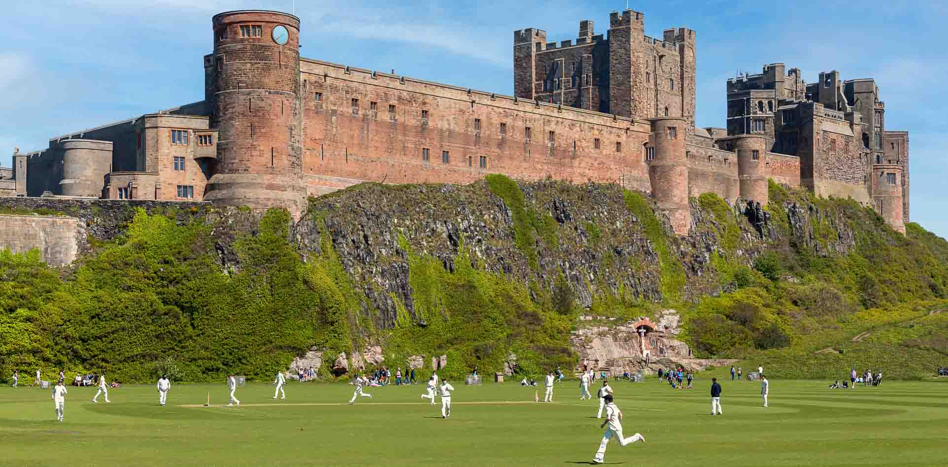 Quintessential English cricket scene, Bamburgh v Ponteland on Bamburgh Cricket pitch in the shadow of Bamburgh Castle.